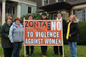 Zonta Members stand with banner: L-R Marcia Bliss, Eileen Healy, Karen Dolce, Jill Colburn, Margie Fuchs and Rosie Papalia
